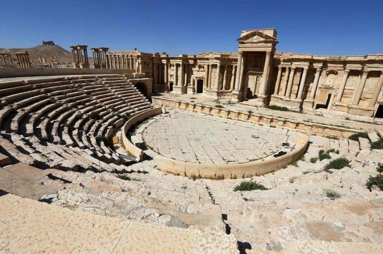 Het amfitheater van Palmyra met op de achtergrond het tetrapylon
